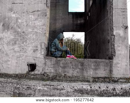 A teenage girl in a hood without a face sits in a rectangular hole of a concrete wall. The concept of teenage problems a homeless child