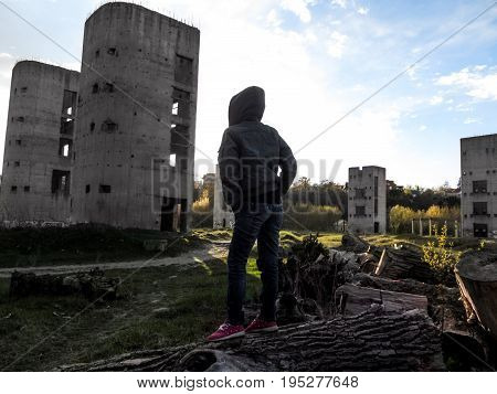 The female silhouette in the hood stands in front of the ruined buildings - the view from the back. A slender person in a jacket and pants stands on the log with his back to the camera and hides her hands in her pockets