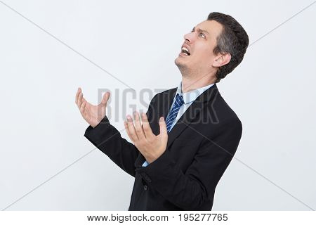 Frustrated businessman shocked with news. Stressful young entrepreneur depressed because of failure. He crying and looking up opposite white background. Despair concept