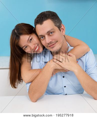 Loving young Asian wife embracing husband from back. Smiling man touching hands of beloved woman and sitting at table. Affection concept