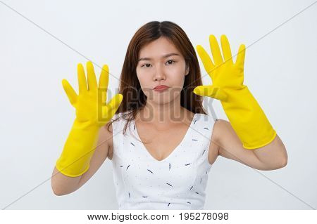 Sad young Vietnamese housewife in rubber gloves showing palms to camera. Portrait of exhausted servant doing housework. Housekeeping concept