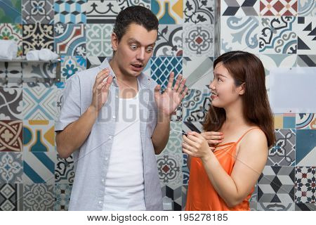 Smiling young Asian woman showing pregnancy test to boyfriend and sharing good news. Shocked husband looking at test and waving hands. Pregnancy announcement concept