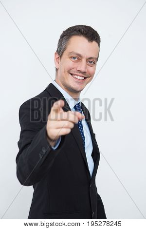Successful male entrepreneur choosing you and pointing with index finger to camera. Cheerful young businessman making order. Business portrait concept