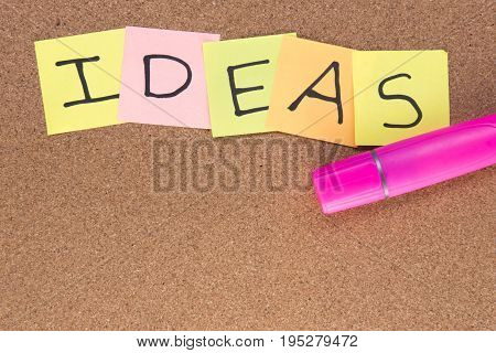 Ideas written on post it notes with a pink highlighter, taken on a wooden background with copy space