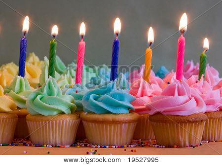 rainbow cupcakes with lit birthday candles
