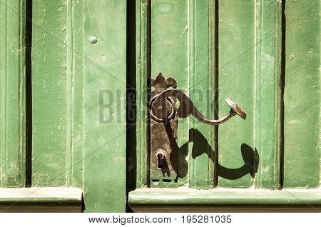 Old green and grunge wooden entrance door with antique door handle.