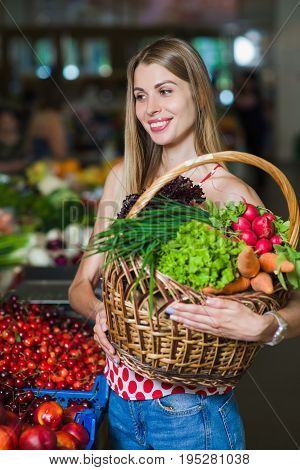 Portrait of a girl with a basket of vegetables. Beautiful blond young girl with a full basket of fruits and vegetables in a vegetable market. Look to the side.