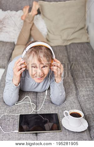 Senior woman listening to ebook for leisure and relaxation