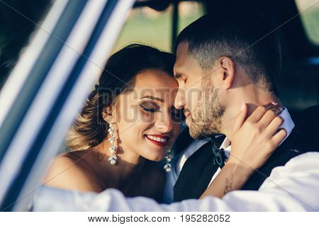 Gentle portrait of the bride and groom in the car.
