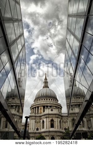 St-Paul's Cathedral and reflection in a mirror wall with a cloudy sky