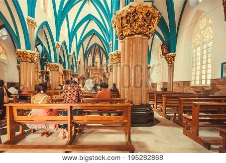 BANGALORE, INDIA - FEB 14, 2017: People inside the beautiful 17th century catholic St. Mary's Basilica with columns on February 14, 2017. Bangalore is the third most populous indian city