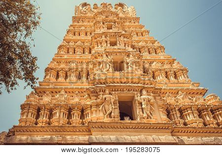 Indian gopuram - tower of tample gate. Traditional Hindu art with reliefs and sculptures in India.
