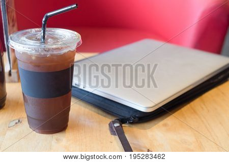 Delicious ice coffee americano with computer laptop on wooden table