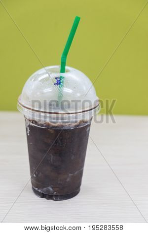 Cola with ice and straw in take away cup on wood table at office
