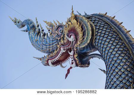Serpent king or king of naga statue in Thai temple isolated on blue backgroundbig snake thai art graphic in the temple(The word naga means