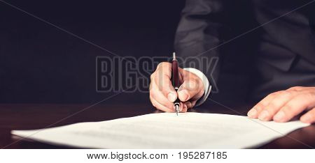 Businessman Signing A Legal Document In His Office