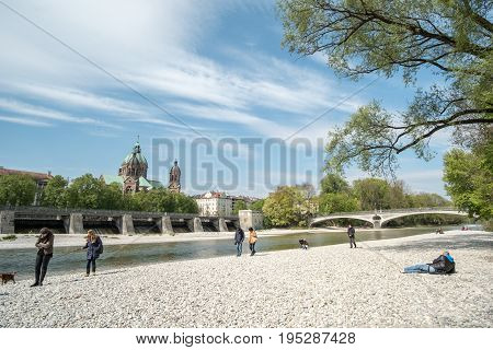 Munich, Germany - 21 April 2017 : View Of People Enjoy Sunny Day At The River Bank Of Isar River In