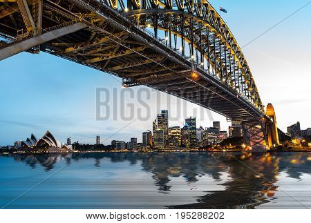 Dramatic widescreen panoramic image of the city of Sydney at sunset with water replaced by digital reflection.