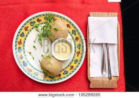 Traditional Lithuanian dishes from potatoes - zeppelins with sauce on a plate