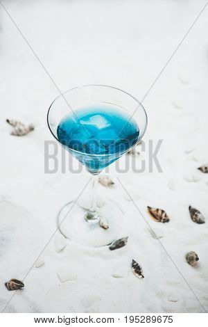close up of blue cool refreshing summer cocktail drink with ice   on white sand with seashells background
