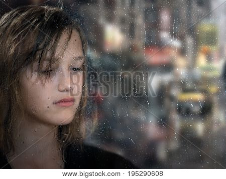 Portrait of a sad girl through the glass. The window in raindrops