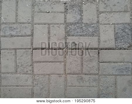 Dirty gray pathway (top view); tiny rubbles and dust; paved with brick stones. For background and texture.