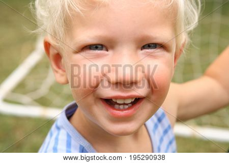 Cute Blonde little boy 4 year old kid face close up smiling and happy in front of soccer net
