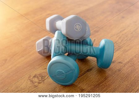 Blue dumb-bells  over wooden gym's floor