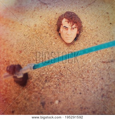 Star Wars character Anakin Skywalker buried in sand with a lightsaber. Anakin Skywalker was quoted for hating sand. 6 inch Hasbro action figure used.