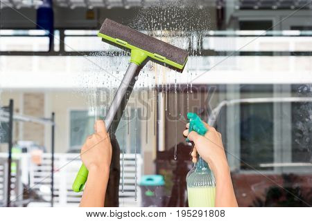 Hands of young woman wipe the glass with a glass cleaner-hobbies and leisure concepts.