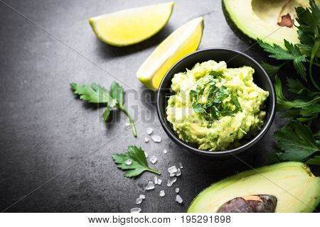 Traditional latinamerican mexican sauce guacamole in a bowl on dark slate background. Top view copy space.