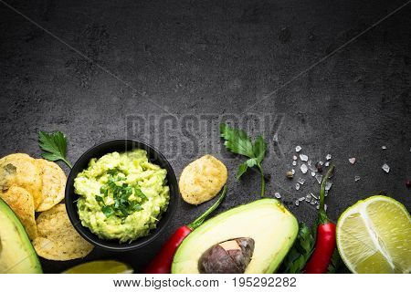 Traditional latinamerican mexican sauce guacamole, chips and ingredients on black slate table. Top view copy space.