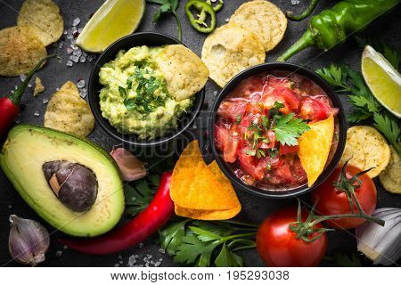 Traditional latinamerican mexican sauce guacamole, salsa, chips and ingredients on black table. Top view.