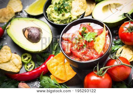 Latinamerican mexican food party sauce guacamole, salsa, chips and ingredients on black table.
