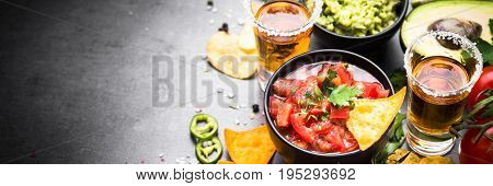 Latinamerican mexican food party sauce guacamole, salsa, chips and tequila on black table. Long banner format.