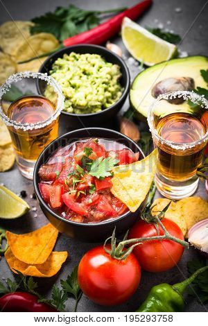 Latinamerican mexican food party sauce guacamole, salsa, chips and tequila on dark table.