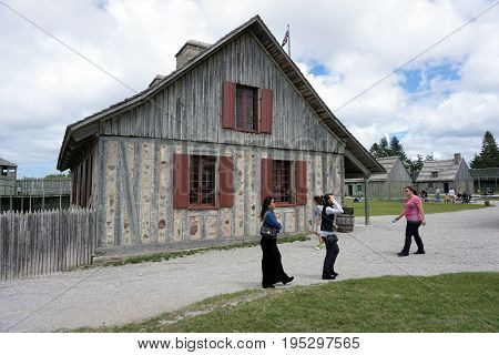 MACKINAW CITY, MICHIGAN / UNITED STATES - JUNE 18, 2017: Tourists enjoy visiting Fort Michilimackinac, in the Colonial Michilimackinac State Park.