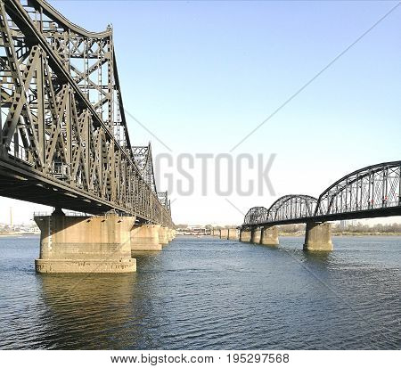 China - North Korea Friendship bridge (left); and the Broken Bridge (right), across the Yalu river. Taken in April, 2017, from public area in Dandong, Liaoning China, opposite to Sinuiju city, DPRK.