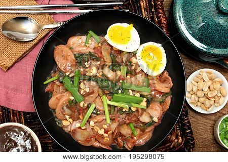 Korean rice cake meal with black bean sauce, roasted peanuts, soft boiled eggs at table overhead.