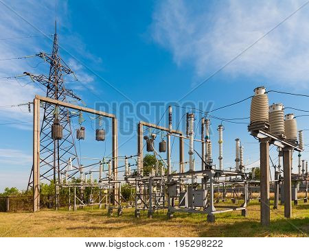 Summer. Electrical substation against the sky with clouds. In the frame insulators transformer wires. Ukraine. Kiev region