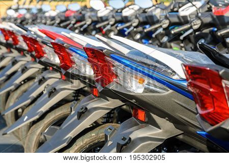 New motorcycles lined up at a store with close up on taillight transportation background