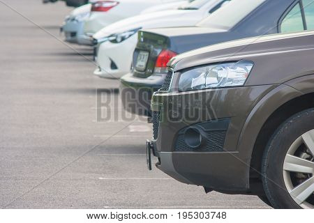 Row of several car parked on parking lot at public park.