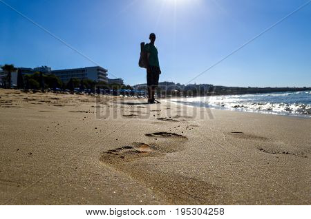 Footprints on the beach close up. Silhouette of a person walking on the beach barefoot