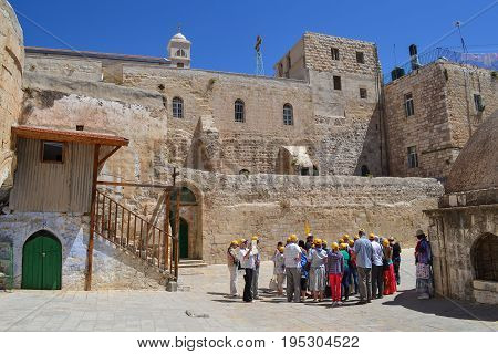 JERUSALEM - May 22: A group of tourists listening to a guide near the Church of the Holly Sepulcher