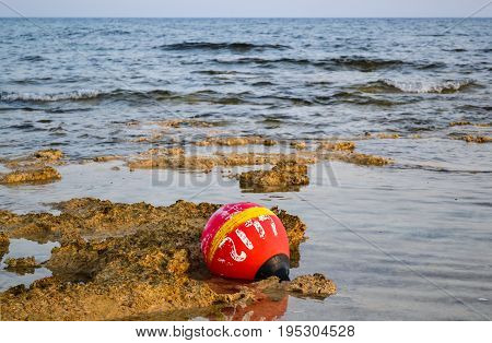 Old buoy of red color thrown ashore