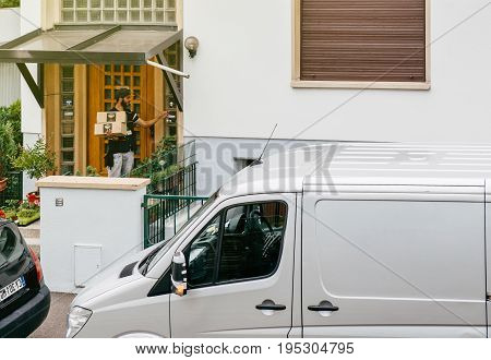 PARIS FRANCE - JUL 12 2017: Delivery worker man holding post parcel box knocking ringing at the doorbell and waiting the consignee to open the door and put the signature in clipboard