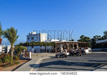 CYPRUS Ayia Napa - September 20 2015: A street cafe. People are having breakfast. On the street is parked a quad bike