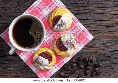Cup of hot coffee and cookies with jam and sugar icing for breakfast on old wooden table top view