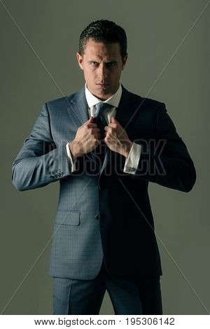 businessman man or successful manager with serious face holding collar in elegant formal suit jacket with white shirt and tie on grey background. Business fashion and success