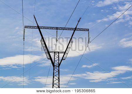Steel electric pylon against the blue sky.